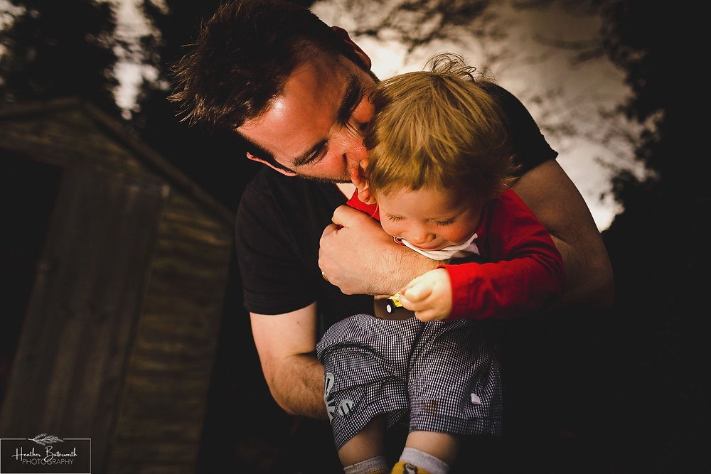 Dad and boy family hug in the garden in Leeds, Yorkshire. Image by Heather Butterworth Photography