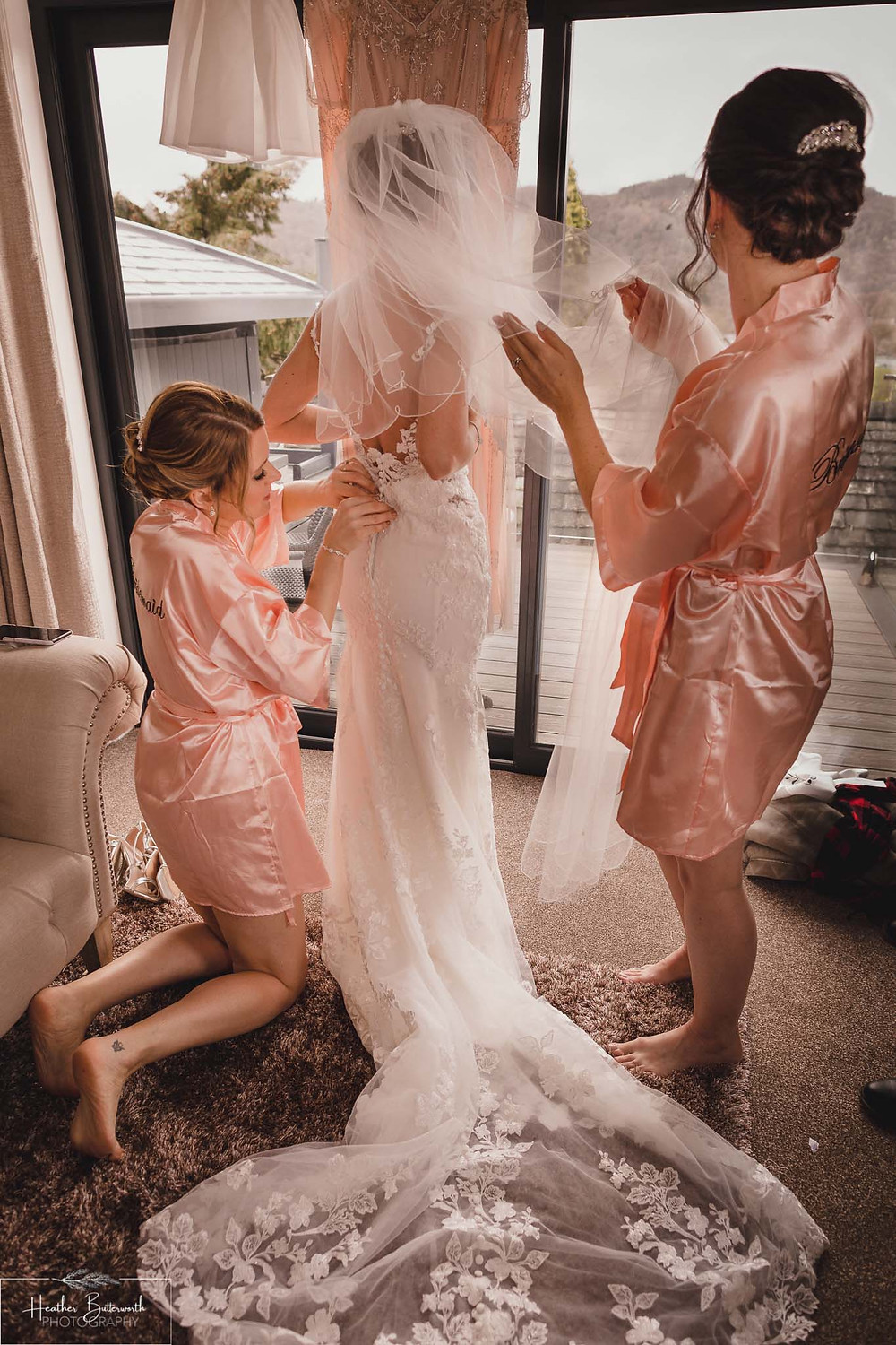 Bride Bex with her bridesmaids who are helping her into her dress and stood by a window during bridal preparations at The Burnside Hotel and Spa in Bowness-on-Windermere