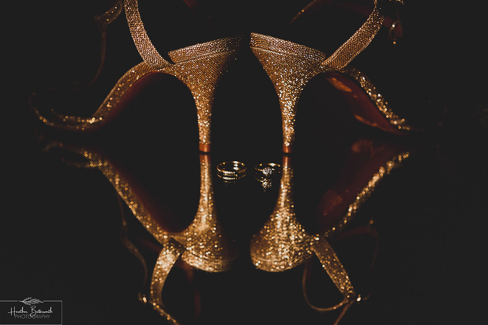 detail of gold glittering shoes and a wedding and engagement ring with a light shining on them