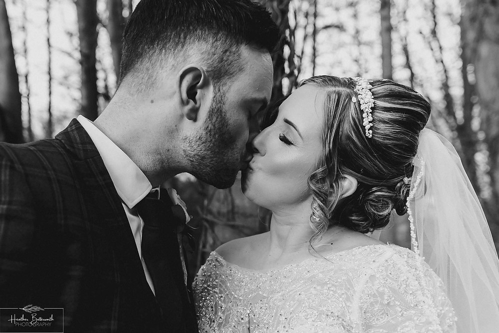 Bride and groom kissing in the woods after their wedding at The Woodman Inn in Thunderbridge near Leeds, Yorkshire