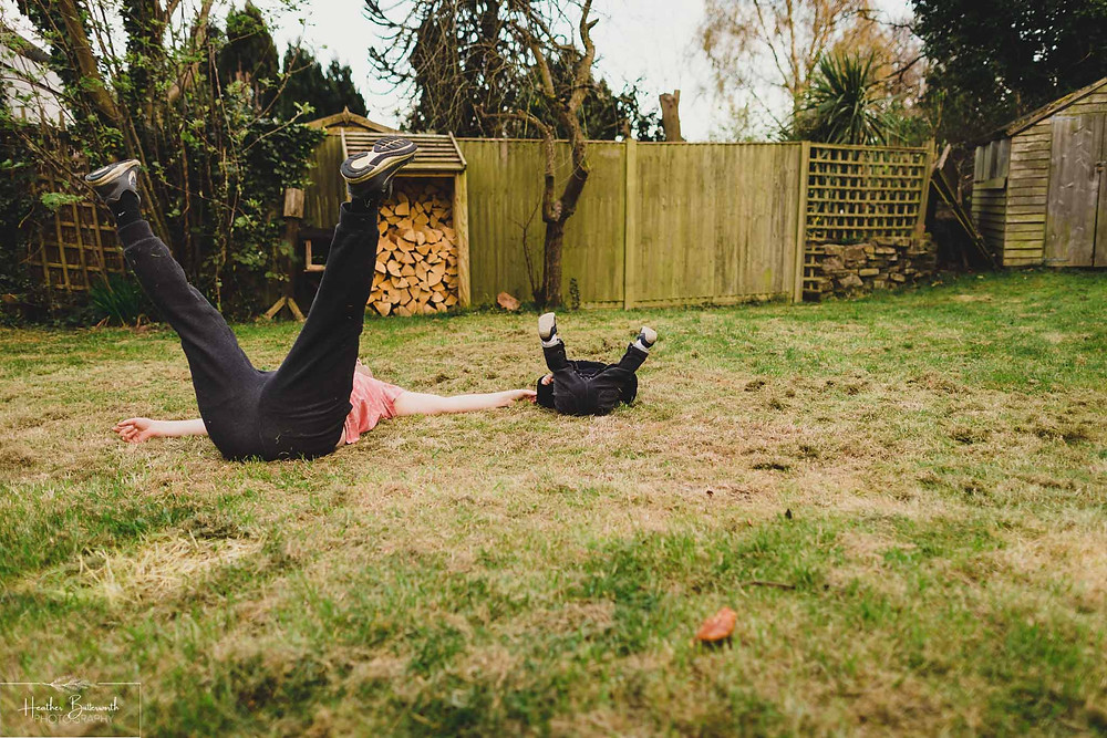 a dad and his son playing in the garden lying on their backs with their legs in the air