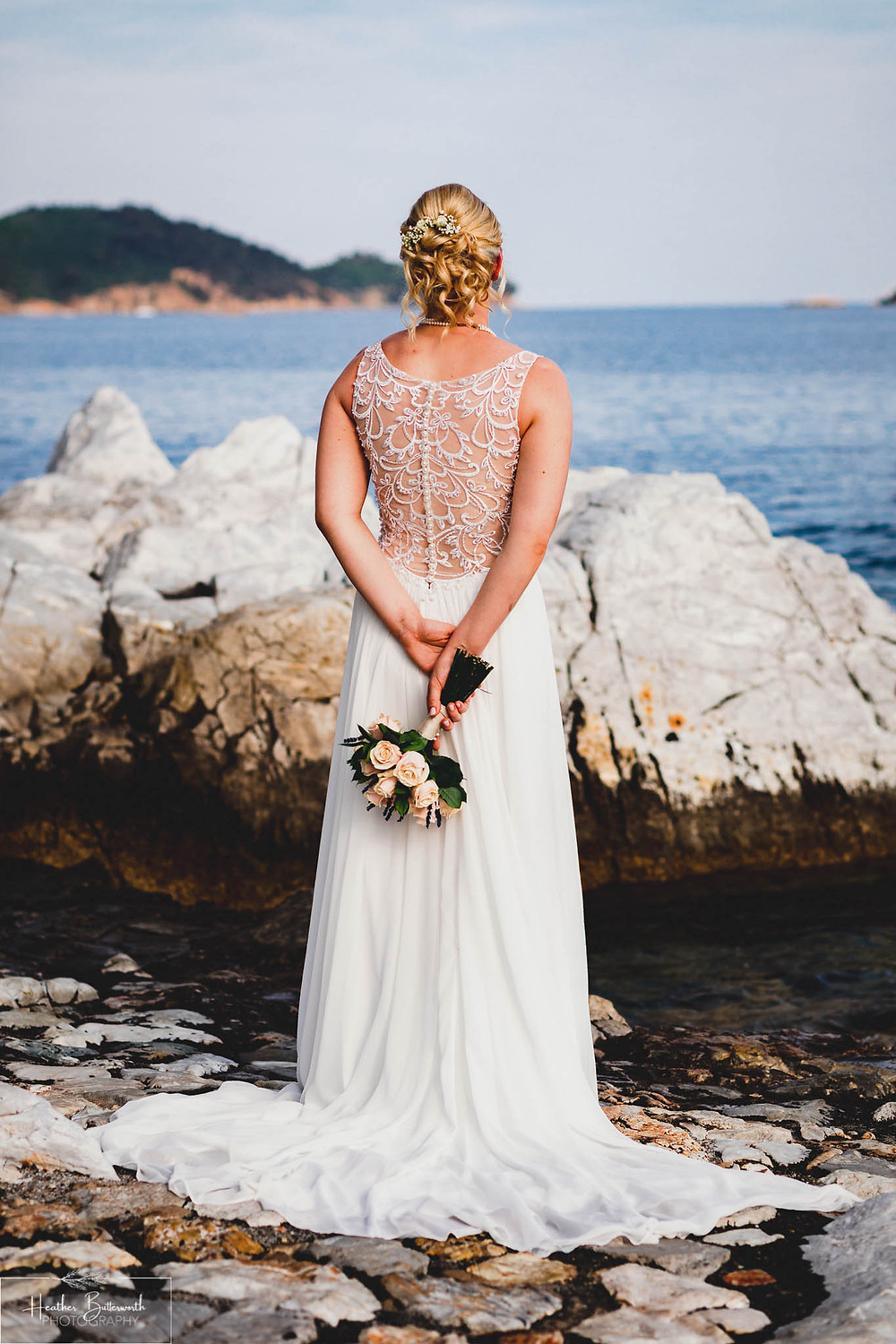bride with her back to the camera showing the detail inter dress on the beach in skiathos