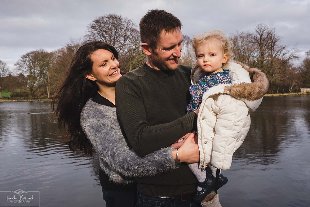 parents stood with their toddler daughter looking at the camera with a lake behind them in roundhay park