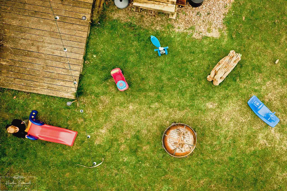 Ariel shot from a drone of a toddler playing in the garden