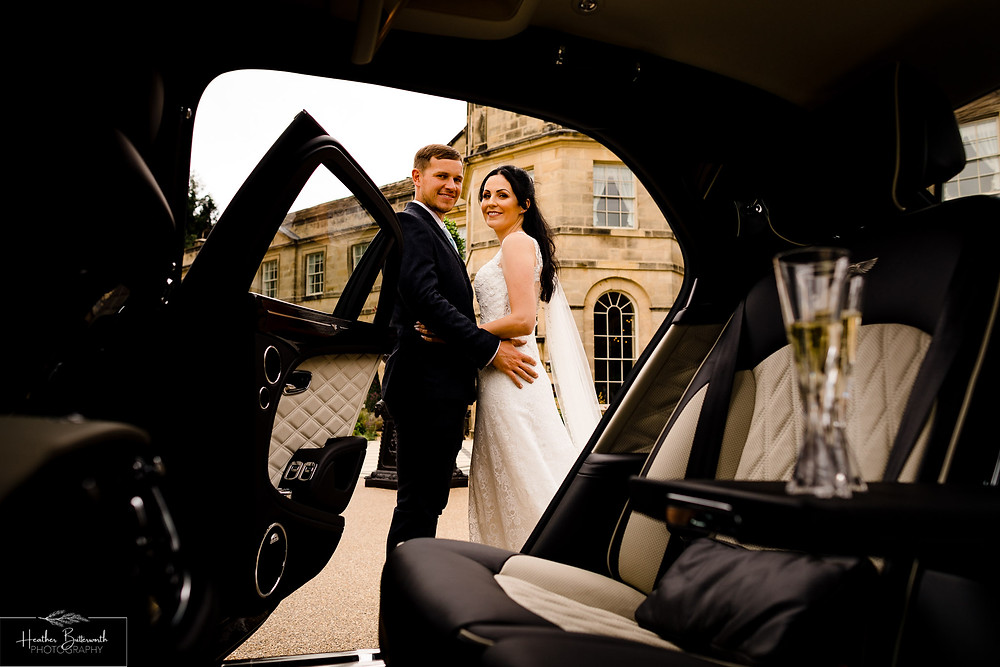 A bride and groom looking into their Bentley Mulsanne outside Grantley Hall, Yorkshire in July 2020