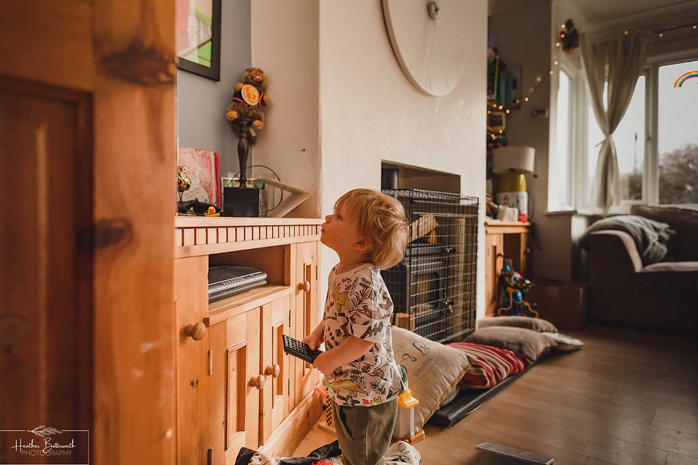 toddler with a remote control looking up at the TV in the living room