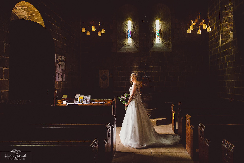 Bride in natural light near the church door after the wedding at Adel Parish Church in Leeds, Yorkshire