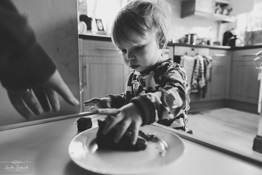 black and white image of a toddler eating chocolate cake with an adult hand reaching in to steal some