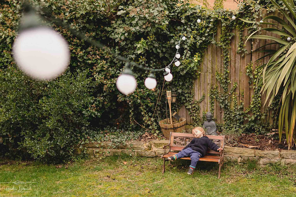 toddler asleep on a tiny bench with outdoor lights hanging above