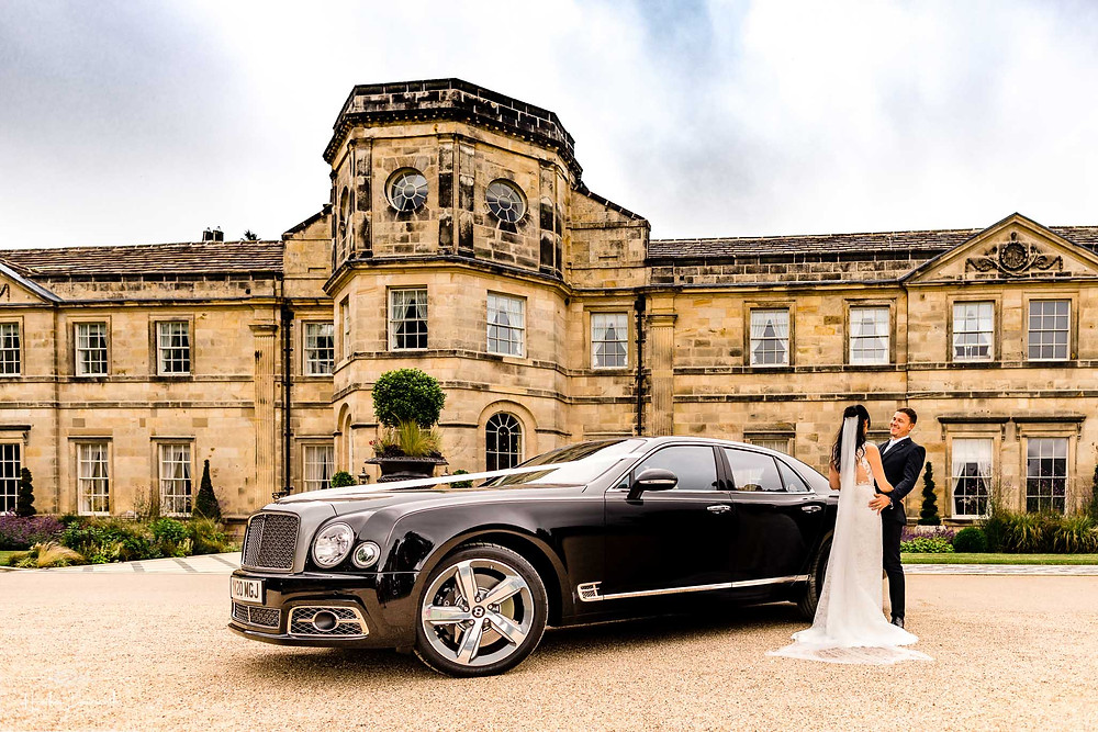 A bride and groom next to their Bentley Mulsanne outside Grantley Hall, Yorkshire in July 2020
