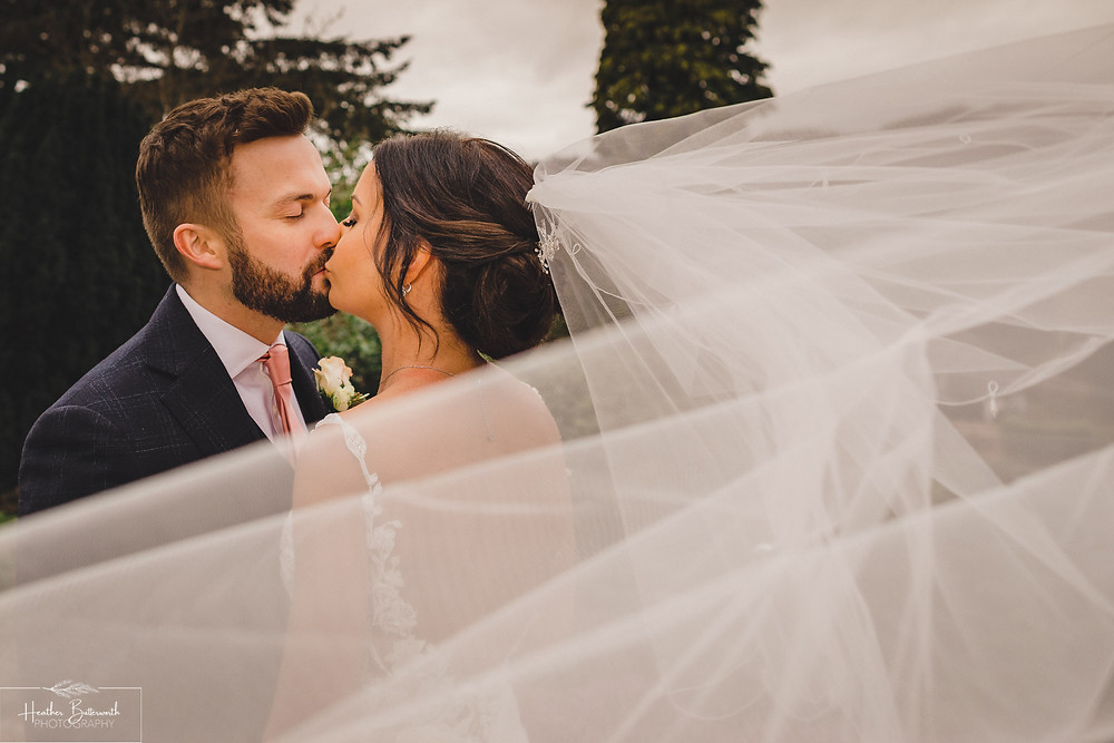 bride and groom kissing with the brides veil wrapped around them