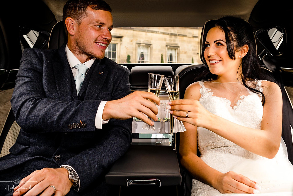A bride and groom drinking champagne in their Bentley Mulsanne outside Grantley Hall, Yorkshire in July 2020