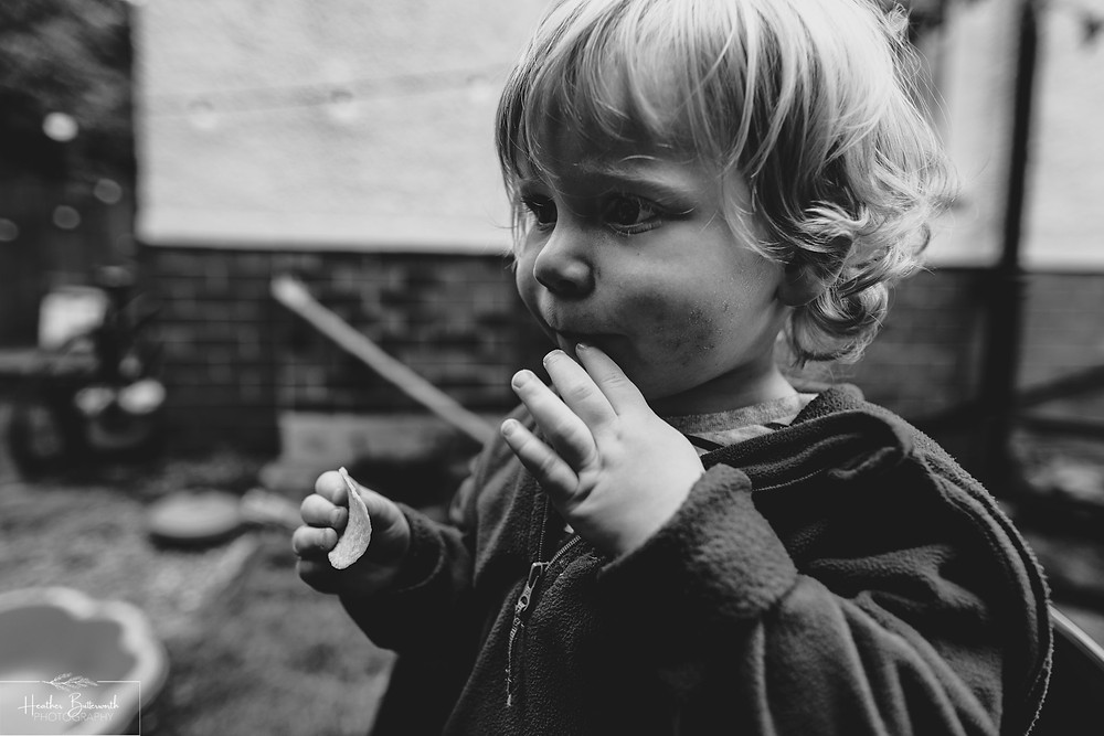 boy eating crisps in a garden in leeds yorkshire in july 2020