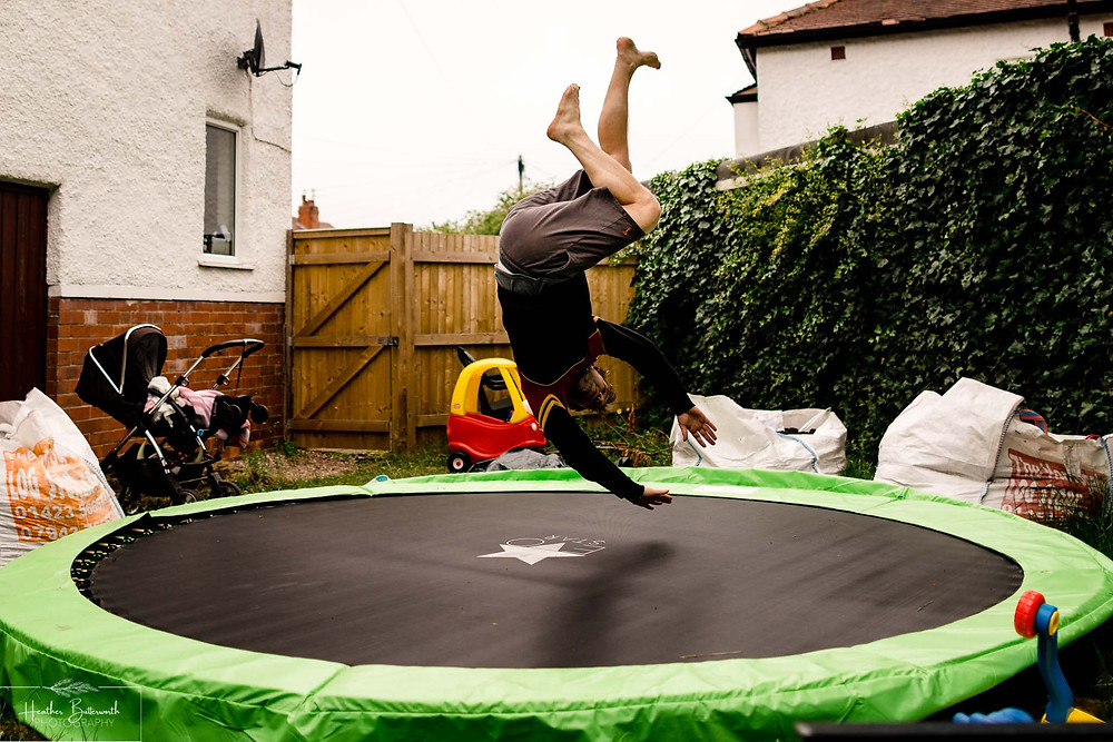 a man upside down after a somersault on a trampoline