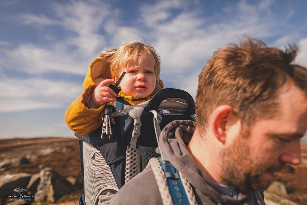 toddler in his dad's back pack on the moorland