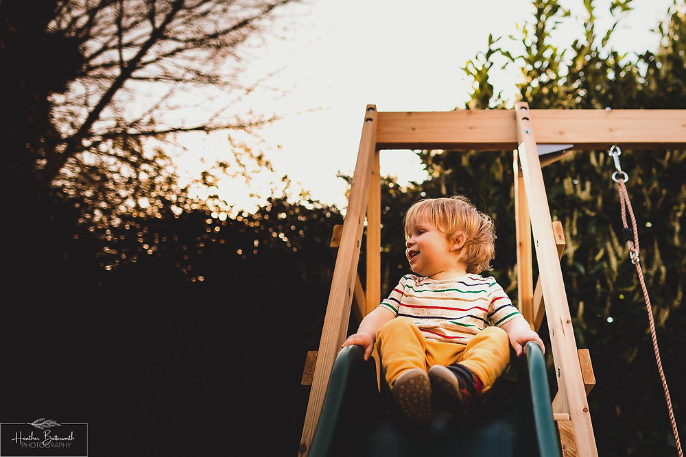 Barney sitting on the slide in his family garden in Leeds, Yorkshire. Image by Heather Butterworth Photography