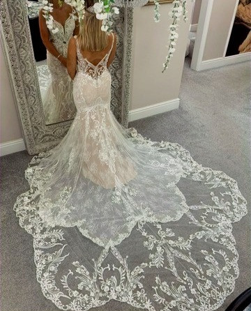 Model wearing a wedding dress and looking in the mirror