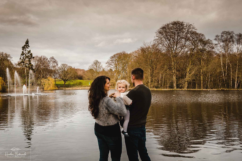 parents stood with their back to the camera with their toddler daughter looking at the camera in roundhay park