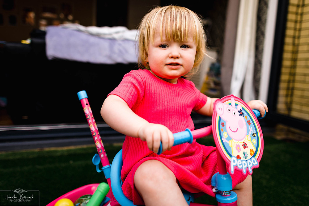 little girl on her new bike at her second birthday party