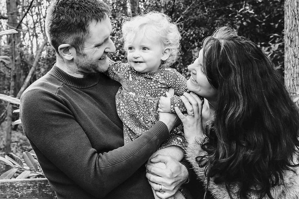 black and white image of parents stood with their toddler daughter in a wood in roundhay park