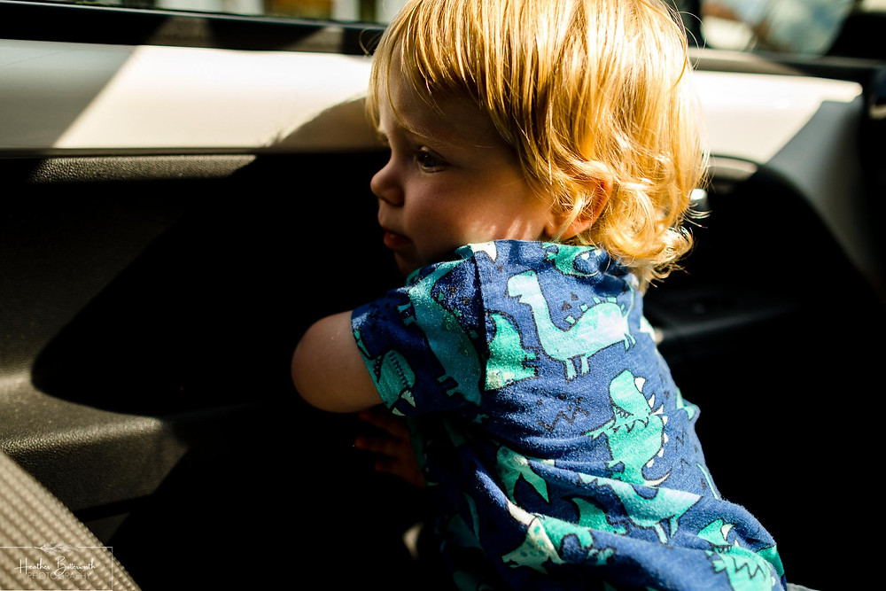 boy playing in a car in the sunshine