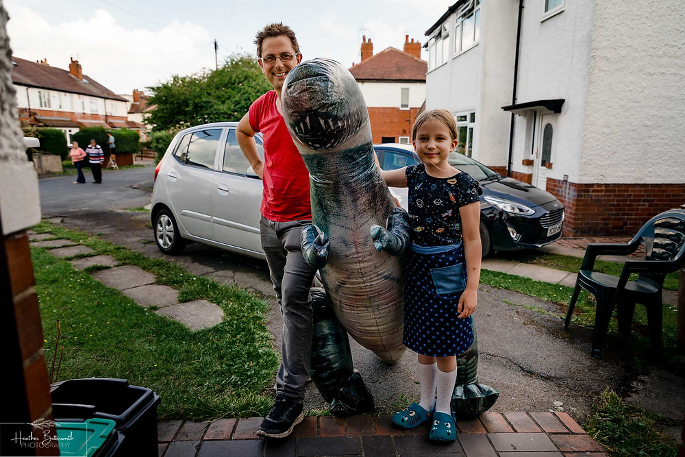 a father and daughter and inflatable dinosaur together after restrictions were slightly lifted after the COVID-19 lockdown in Leeds , Yorkshire in June 2020