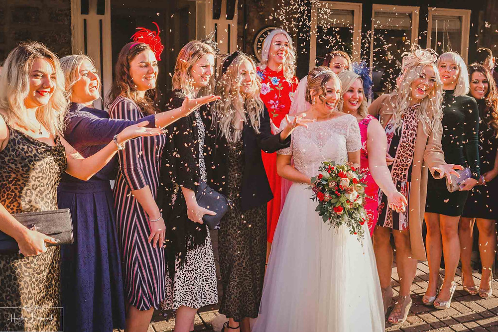 confetti thrown by brides friends at the bride at her wedding at the woodman inn in Yorkshire UK
