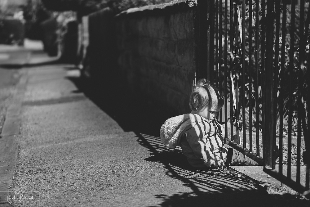 documentary family photography taken during lockdown in 2020 in Leeds Yorkshire by Photographer Heather Butterworth of a boy sat under a gate