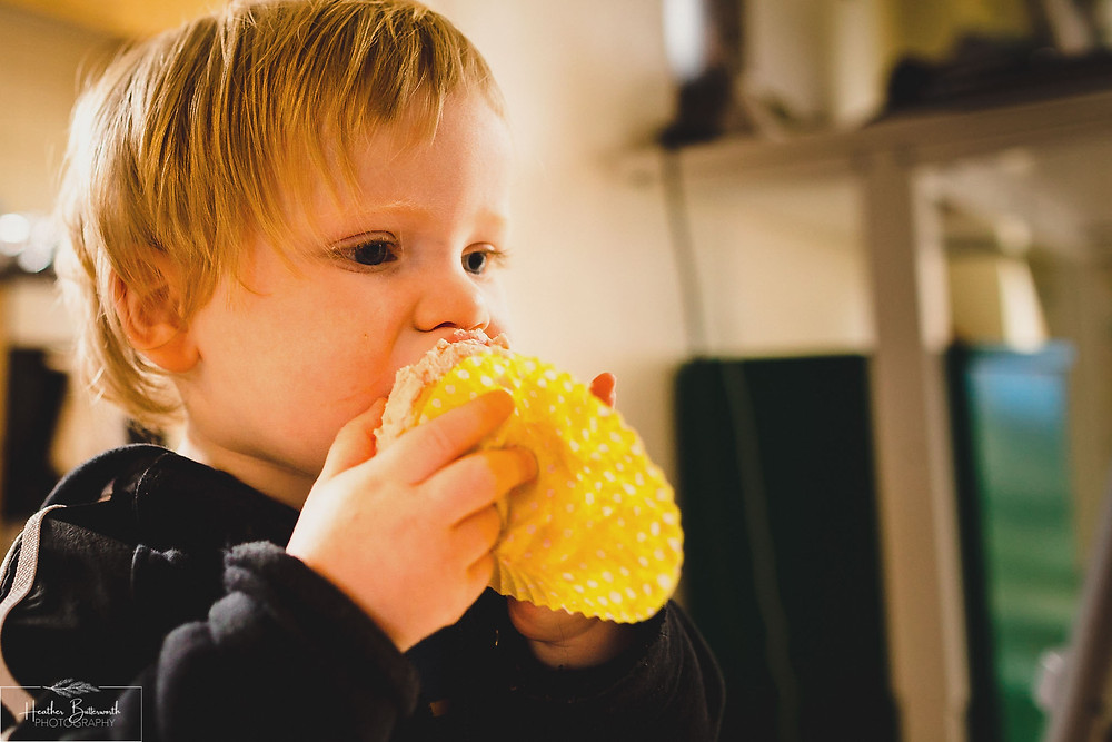 Boy eating cupcakes made in Leeds, Yorkshire. Image by Heather Butterworth Photography