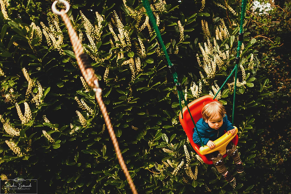 Barney playing on the rope swing in his family garden in Leeds, Yorkshire. Image by Heather Butterworth Photography