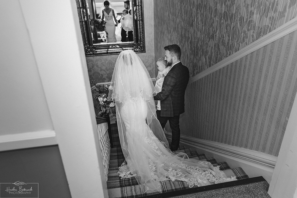 Bride Bex with her new husband Andy and baby daughter walking down the stairs in monochrome at The Burnside Hotel and Spa in Bowness-on-Windermere