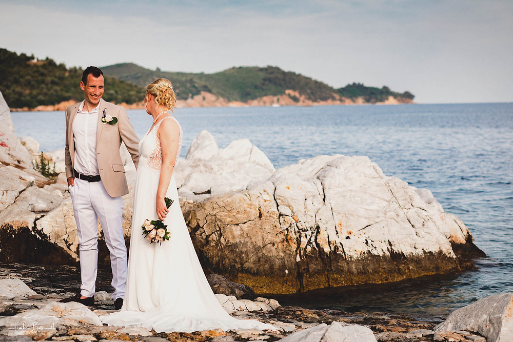 bride and groom on the beach in skiathos with the blue sea behind them