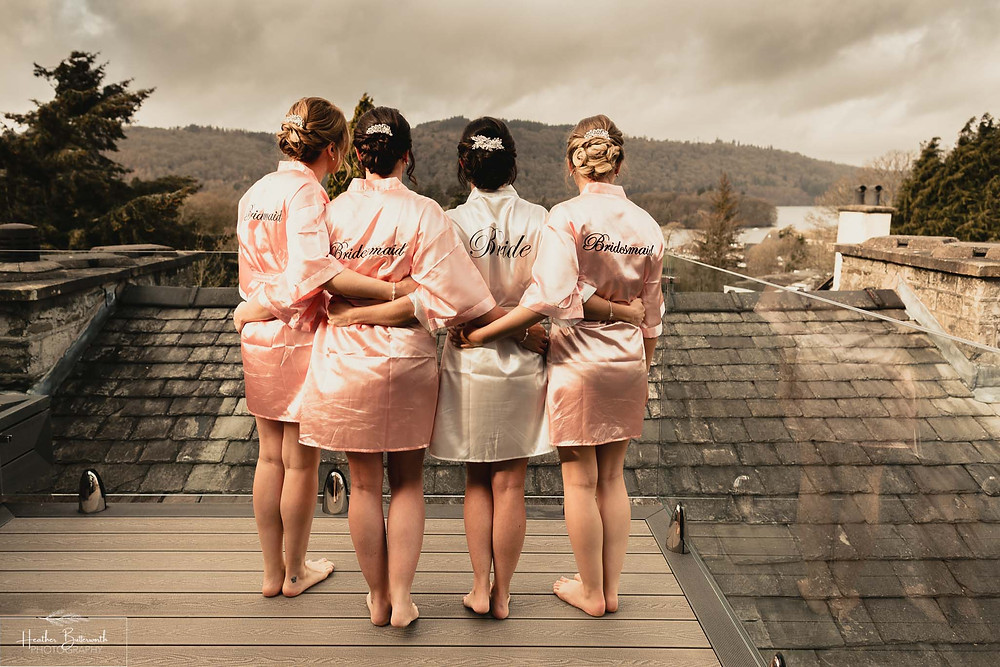 Bex the bride and her bridesmaids stood on the balcony overlooking lake windermere in their silk robes during bridal preparations at The Burnside Hotel and Spa in Bowness-on-Windermere