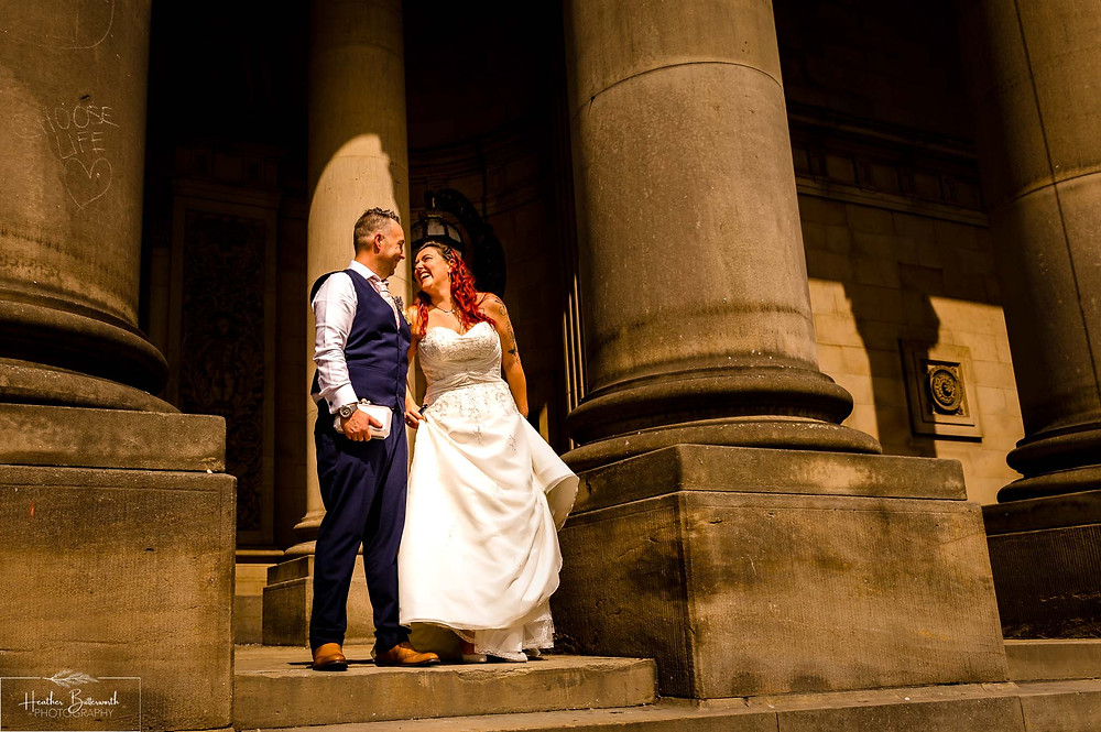 bride and groom on the steps at Leeds Town Hall after their wedding august 2020