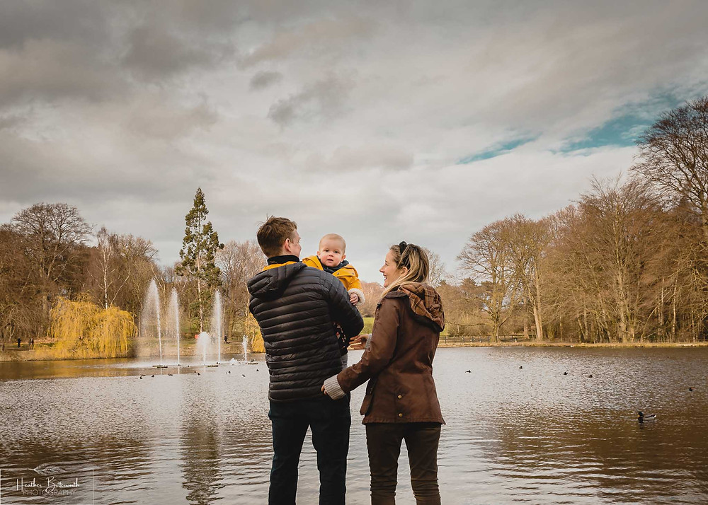 parents stood with their back to the camera with their toddler son looking at the camera in roundhay park