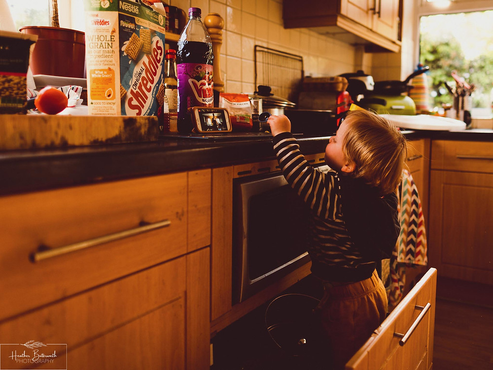 documentary family photography taken during lockdown in 2020 in Leeds Yorkshire by Photographer Heather Butterworth of a toddler in a kitchen drawer