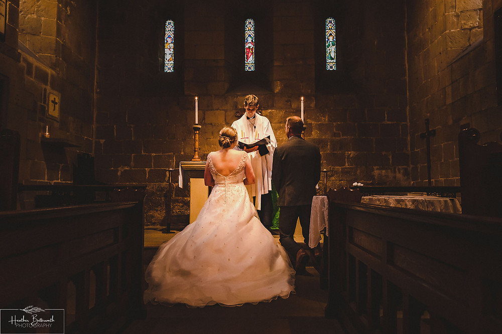 Bride and Groom at the alter in Adel Parish Church in Leeds, Yorkshire