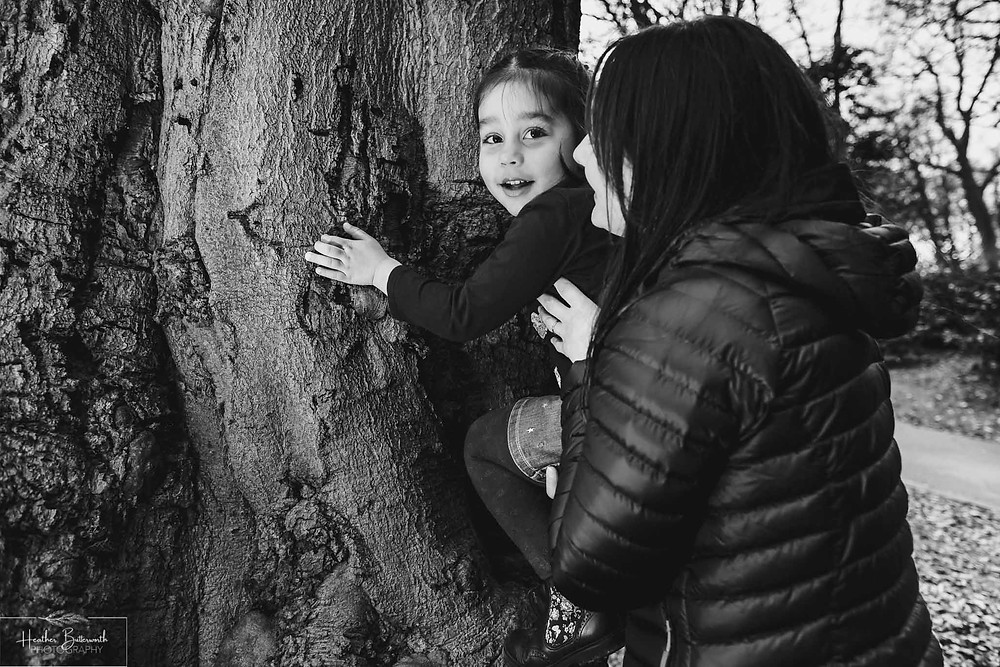 young girl climbing a tree in roundhay park with her mum black and white image