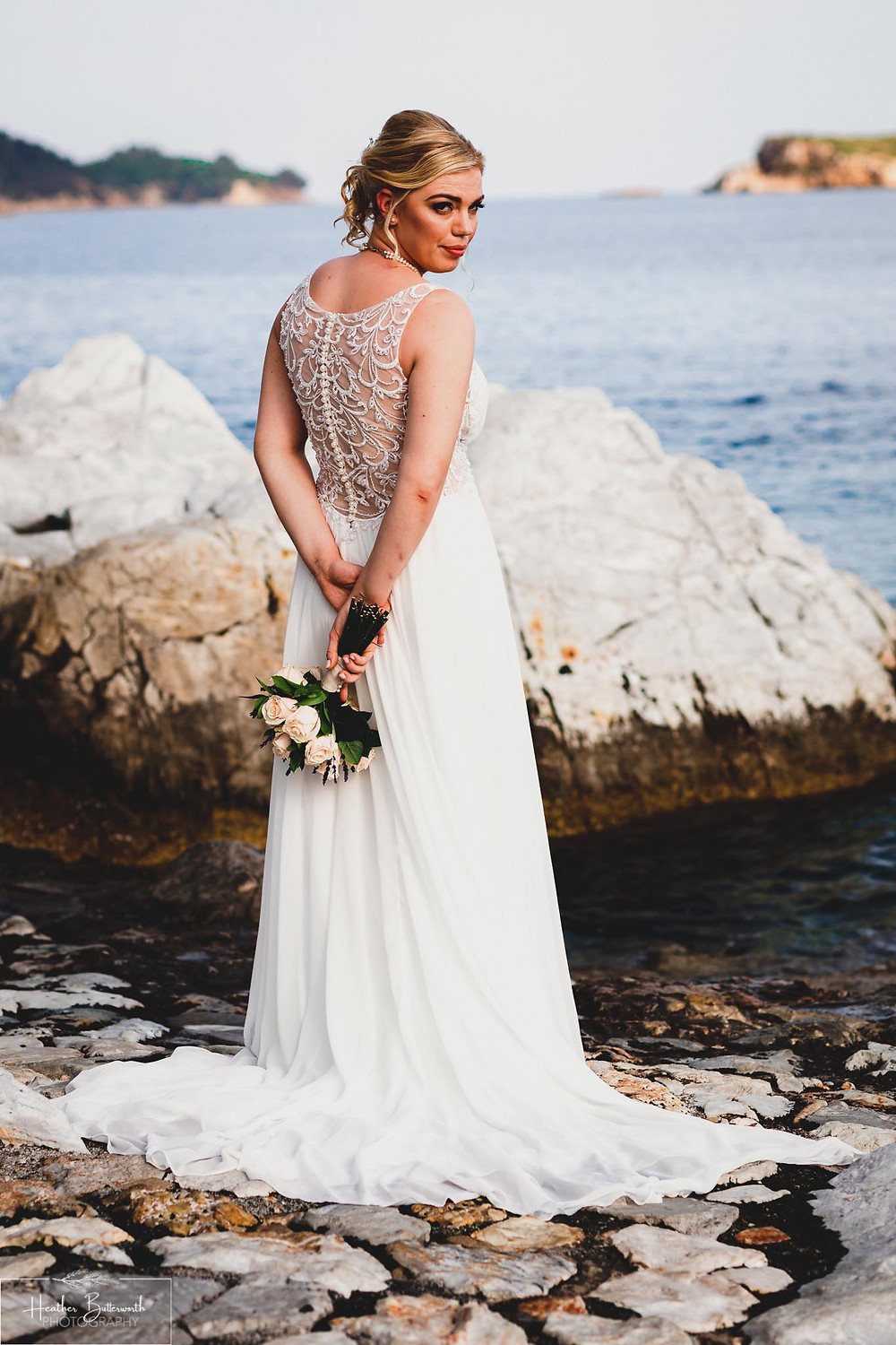 Bride on the beach looking around after her wedding at The Bourtzi in Skiathos Town, Greece