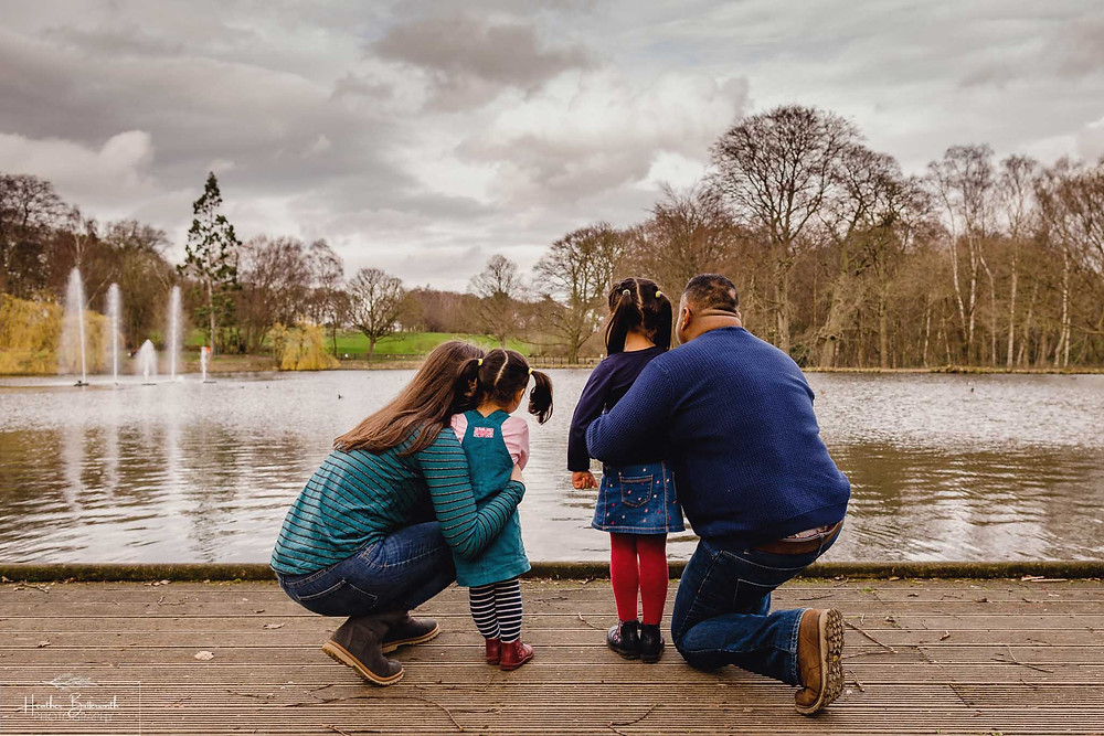 parents stood with their back to the camera looking out at a lake with their two young daughters also with their back to the camera in roundhay park