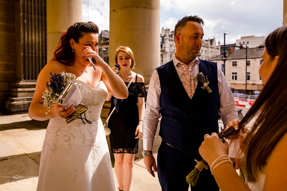bride and groom greeting family after their wedding ceremony at Leeds Town Hall in August 2020