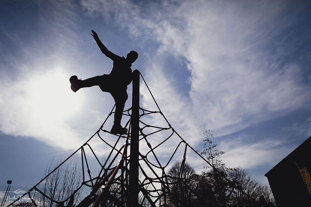 silhouette of a man on top of a climbing frame
