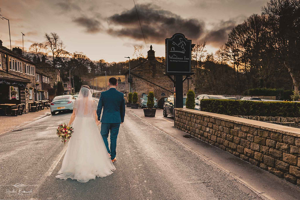 Bride and groom walking down the road together after their wedding at The Woodman Inn in Thunderbridge near Leeds, Yorkshire