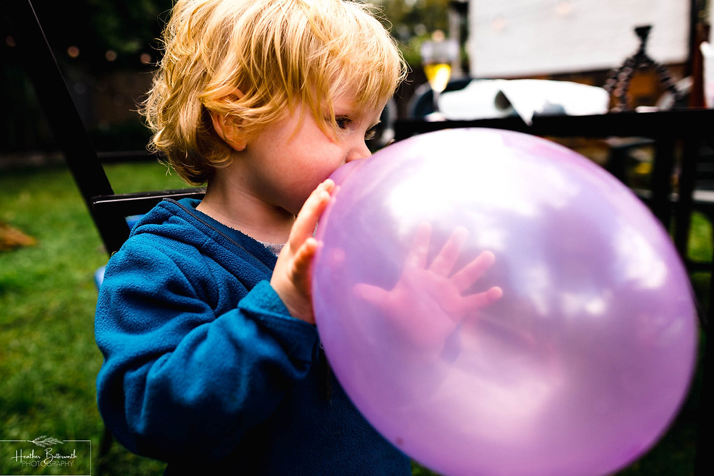 boy blowing up a balloon in a garden in leeds yorkshire in july 2020