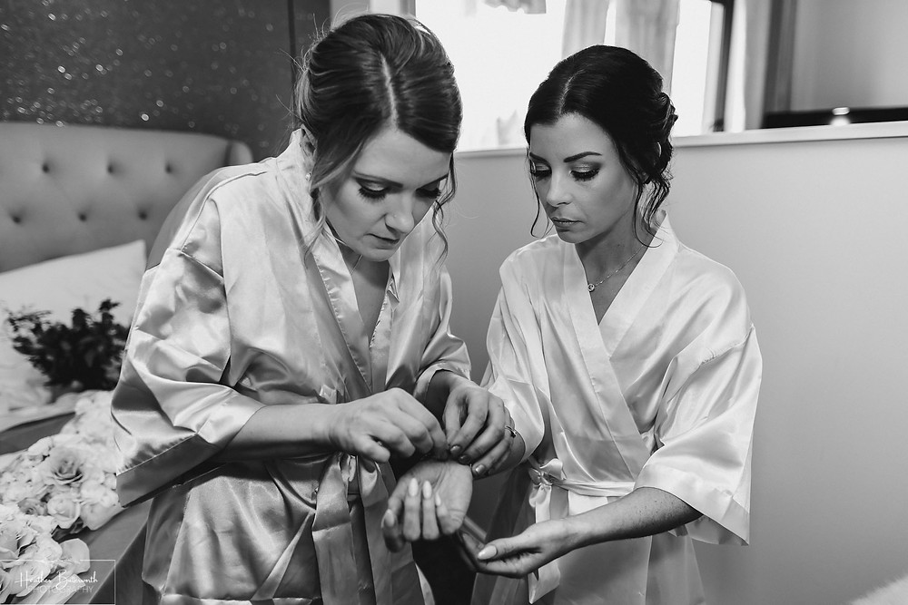 Bex the bride and her bridesmaid in their silk robes during bridal preparations at The Burnside Hotel and Spa in Bowness-on-Windermere