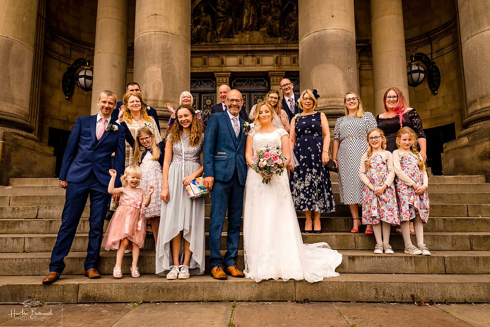 Bride and groom & wedding guests at Leeds Town Hall after their wedding in august 2020