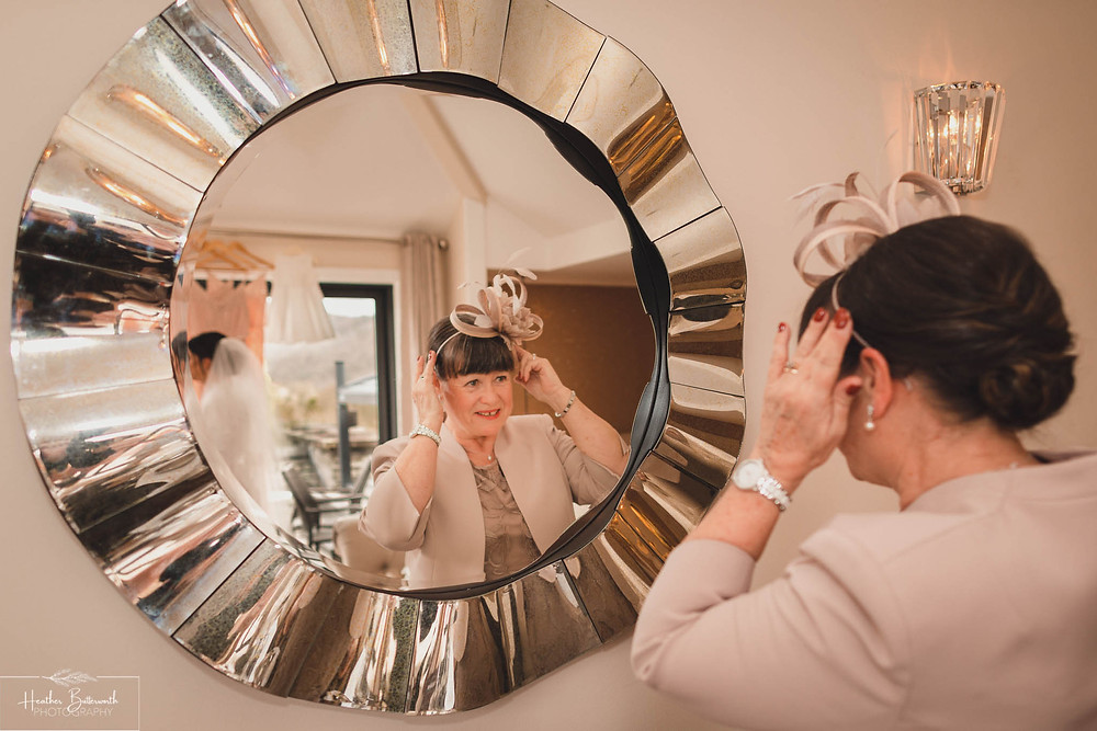 Mother of the bride looking in the mirror during bridal preparations at The Burnside Hotel and Spa in Bowness-on-Windermere
