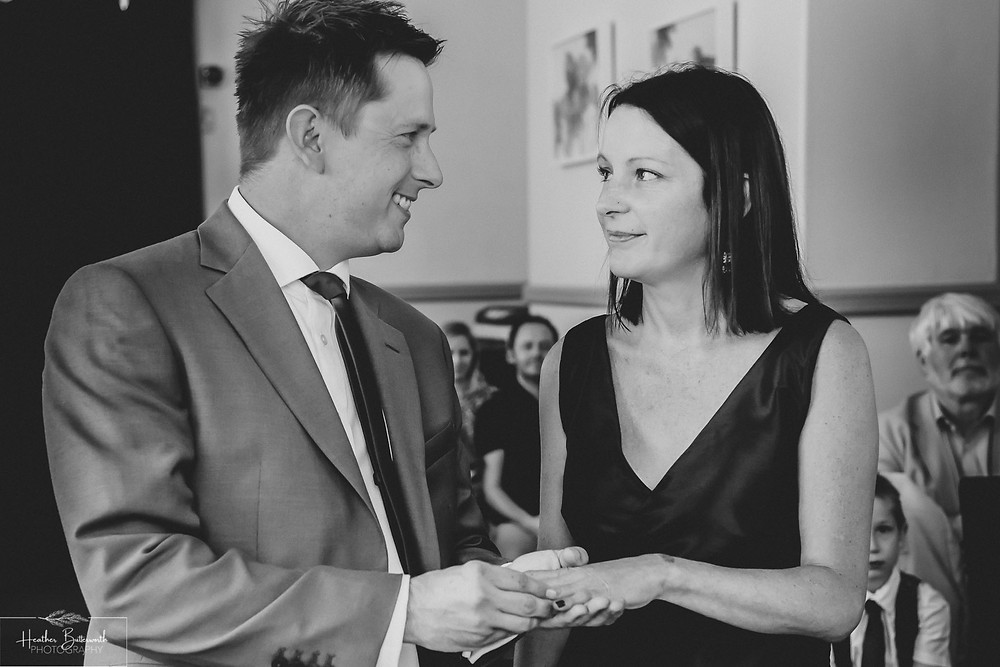 Bride and groom looking happily at each other and exchanging rings during their wedding ceremony at Leeds Town Hall, Yorkshire