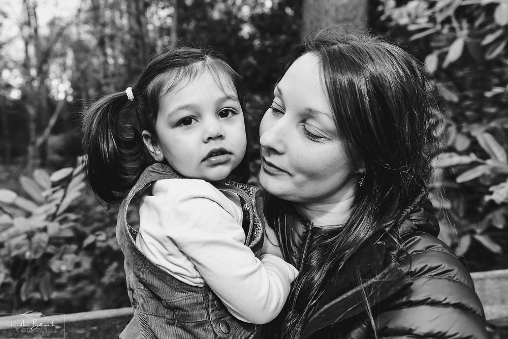 black and white image of a mum and daughter together in a wood with trees in the background in roundhay park