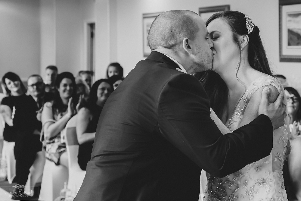 Bride and grooms first kiss during their wedding ceremony at Hollins Hall in Baildon, Yorkshire